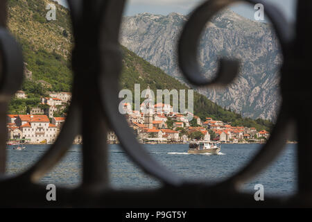 View through decorative window ironwork old town of Perast on the Bay of Kotor off the Adriatic in Montenegro showing Sveti Nikola church bell tower - Stock Photo