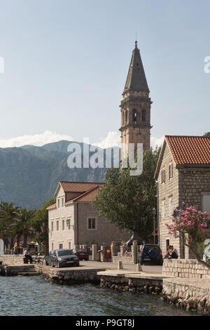 Front at town of Perast on the Bay of Kotor off the Adriatic in Montenegro on a summers day showing the Sveti Nikola church bell tower and mountains. - Stock Photo