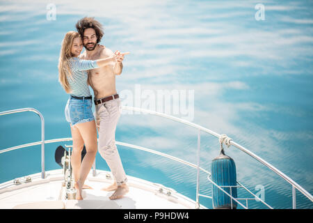 Passionate loving caucasian couple dancing on bow of sailboat, over blue sea background with copyspace. Summer vacation, People Relations and Love, Ro - Stock Photo