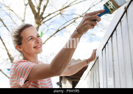 young, pretty woman strokes the garden fence with white paint in summer - Stock Photo