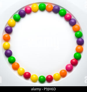 Circle of colored glazed candies on white background. candies melting in several rows, forming a rainbow - Stock Photo
