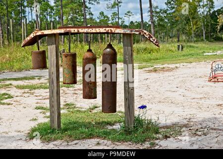 Huge homemade wind chimes made from cylinders hang outside in a wooded area - Stock Photo