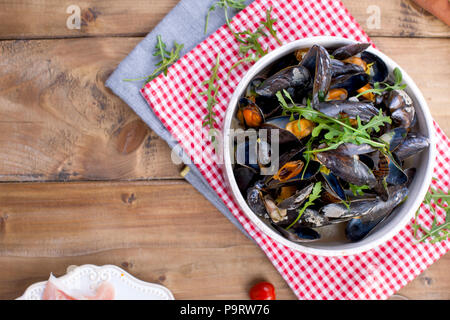 Muesli in a white ceramic bowl, on a red napkin. On a wooden background. Free space for text or advertising - Stock Photo