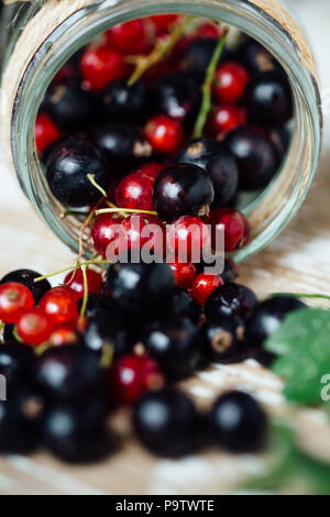 Fresh ripe red and black currants on the background of a wooden table. Wooden background - Stock Photo