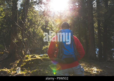 hiking man with blue backpack and red sweater in the forest - Stock Photo