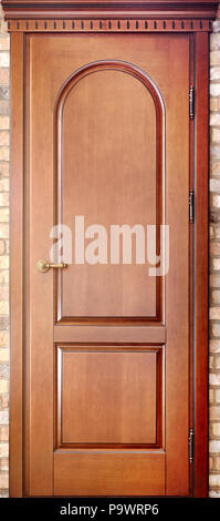 Wooden interroom carved door in a door frame made of maple tree with brass handle with geometric ornaments on brick background - Stock Photo