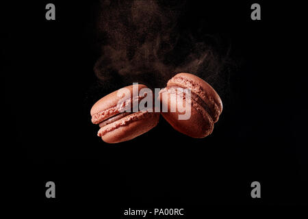 French chocolate macaron with cocoa powder against black background - Stock Photo