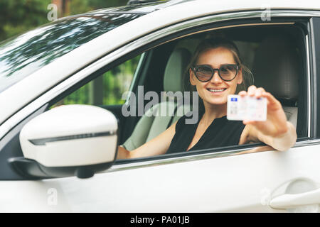 happy young woman showing her driver license through the car window - Stock Photo