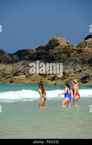 Three young women in swimsuits walking into the sea on a hot summer's day on Porthmeor beach at St Ives in Cornwall - Stock Photo