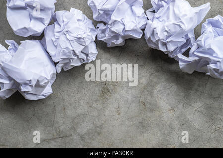 crumpled paper balls on a gray concrete surface - Stock Photo