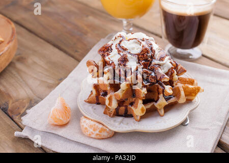Sweet Belgian waffles for breakfast, decorated with white cream and chocolate sauce. Glass with coffee black and orange juice, fruit bananas and grapfruit on a brown wooden background. free space for. - Stock Photo
