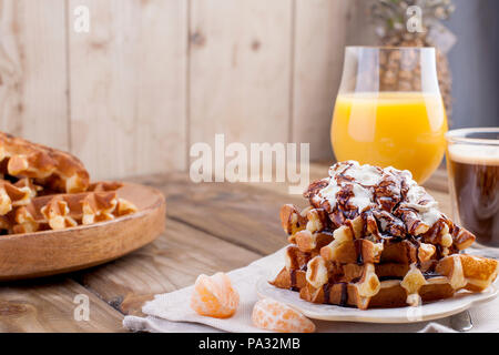 Sweet Belgian waffles for breakfast, decorated with white cream and chocolate sauce. Glass with coffee black and orange juice,fruit bananas and grapfruit. Free space for text or advertising. - Stock Photo