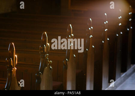 Row of church pews with fluer de lys carvng with atmospheric lighting. - Stock Photo