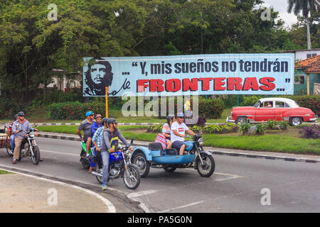 Cuban people in cars and motorcycles in front of propaganda billboard sign depicting Che Guevara, y mis suenos no tendran fronteras, Vinales, Cuba - Stock Photo
