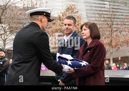 160315-N-LR347-004 NEW YORK (March 15, 2016) U.S. Navy Senior Chief Operations Specialist Ryan King from the U.S. Navy Ceremonial Guard presents a flag flown at Arlington National Cemetery to Heidi Hayden, right, U.S. Marine Corps veteran and chief people officer for the 9/11 Memorial and Museum as Joe Daniels, president of the 9/11 Memorial and Museum looks on. The flag was presented to the 9/11 Memorial and Museum for their dedicated work honoring the historic bond between the Navy and the city of New York that was only deepened by the terrorist attacks of 9/11. (U.S. Navy photo by Lt. Matth - Stock Photo