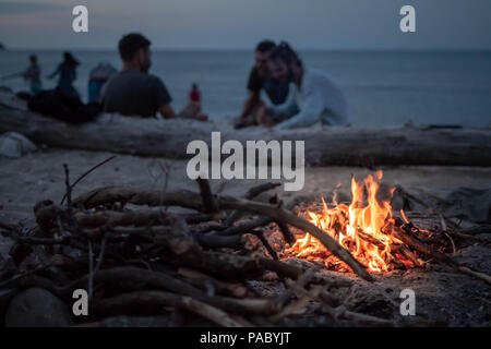 Bonfire on the beach by the sea at dusk with a group of friends in the background - Stock Photo