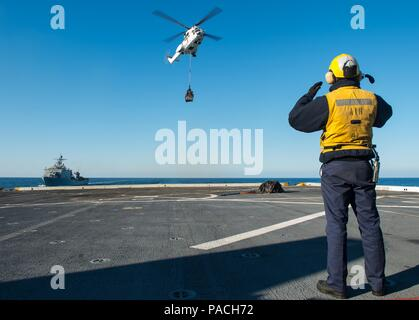 160315-N-GR718-076  EAST SEA (March 15, 2016) Aviation Boatswain's Mate (Handling) 3rd Class Elliot Salgado, from Brooklyn, New York, signals an EH-96 Puma on approach to amphibious transport dock ship USS New Orleans (LPD 18) while completing a vertical replenishment (VERTREP). USS New Orleans is assigned to the Boxer Amphibious Ready Group and is participating in Exercise Ssang Yong 2016. Ssang Yong is a biennial combined exercise conducted by forward deployed U.S. Forces with the Republic of Korea Navy and Marine Corps, Australian Army and Royal New Zealand Army Forces in order to strengthe - Stock Photo