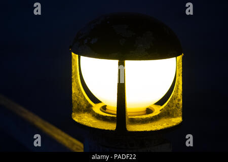 Close up of vintage bollard lamp on wooden railing with bokeh background in night time, selective focus. - Stock Photo