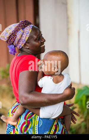 LIBREVILLE, GABON - MAR 6, 2013: Unidentified Gabonese woman carries her little baby child on her arms in Gabon, Mar 6, 2013. People of Gabon suffer o - Stock Photo