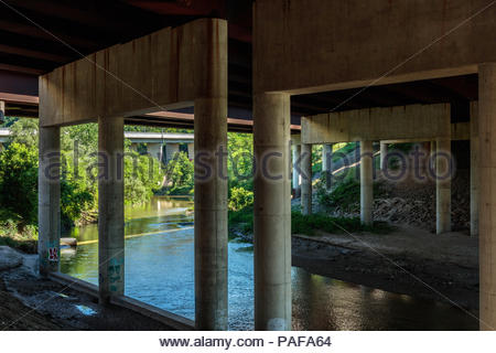 Rouge River flows under the Highway 401 girder bridge in Rouge National Urban Park in Toronto Ontario Canada - Stock Photo