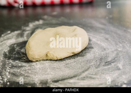 Mound of wheat flour on top of black granite table, preparation of pizza dough. - Stock Photo