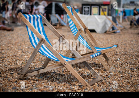 Two deckchairs sit on a pebble beach facing the sea in Brighton, UK - Stock Photo
