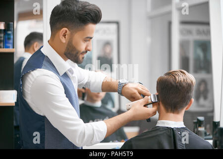 Barber doing new haircut for young client sitting in front of mirror. Wearing white casual shirt, grey waistcoat, watch. Looking concentrated, loving his job. Model covered with special black cape. - Stock Photo