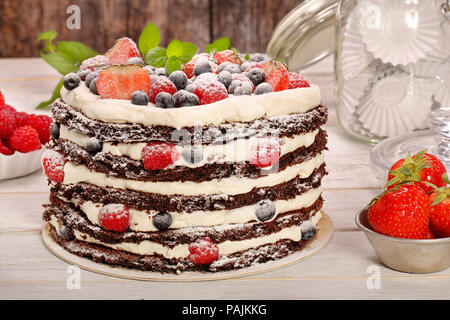 Chocolate cake with white cream and fresh fruits on wooden background - Stock Photo