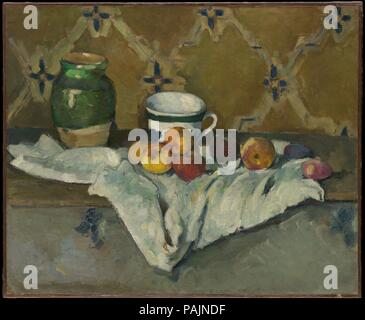 Still Life with Jar, Cup, and Apples. Artist: Paul Cézanne (French, Aix-en-Provence 1839-1906 Aix-en-Provence). Dimensions: 23 7/8 x 29 in. (60.6 x 73.7 cm). Date: ca. 1877.    In addition to apples--a favorite motif of Cézanne's--the ceramic jar and cup seen in this still life feature in numerous paintings by the artist. The wallpaper in the background appears in six works that he painted about 1877, when he rented an apartment at 67 rue de l'Ouest, Paris. Its pattern is echoed both by the shape of the white cloth on which the everyday items are arranged and by the painted floral decoration o - Stock Photo