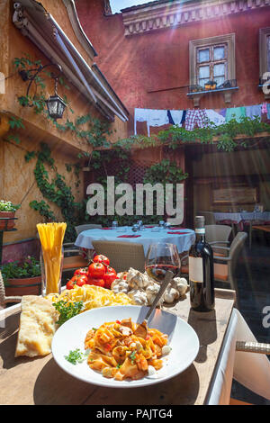 sunlit plate of Italian pasta with basic ingredients around served in restaurant - Stock Photo