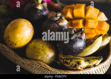 Fruit plate with mango, passion fruit, mangosteen, dragonfruit on wooden table - Stock Photo