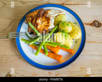 Lunch  a quarter roast chicken  with new potatoes carrots, green beans and chopped chives on a wooden table top - Stock Photo