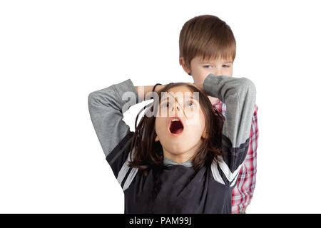 A little brother pulls the hair of his older sister.  He looks sly and mischievous.  She grabs her head with an open mouth look of shock and pain. - Stock Photo