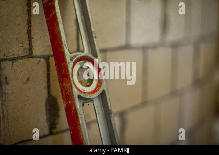Close up of a spirit level leaning on a blurry brick wall - Stock Photo