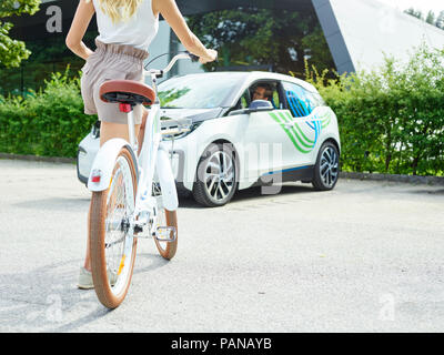 Woman with bicycle in front of electric car - Stock Photo