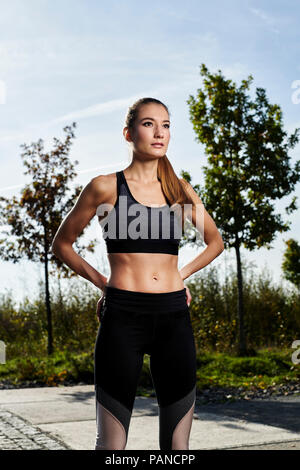 Portrait of confident sportive young woman - Stock Photo