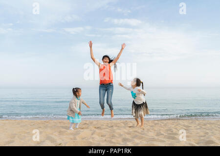 Happy mother with two daughters playing on the beach - Stock Photo