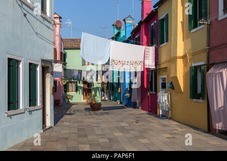 Italy, lagoon of Venice, Burano, colorful houses and laundry hanging out to dry - Stock Photo
