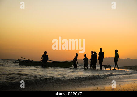 Fishermen Group & Dog Silhouette Bringing a fishing boat to the beach during orange island sunset- Alona Beach, Bohol - Philippines - Stock Photo