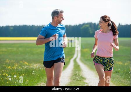 Couple running on field path - Stock Photo