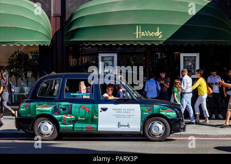 A Traditional London Taxi With Harrods Branding Outside Harrods Department Store, Brompton Road, Knightsbridge, London, England - Stock Photo