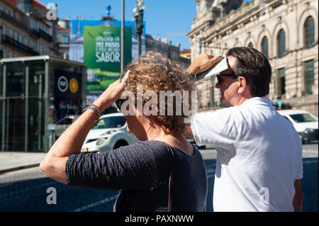 14.06.2018, Porto, Portugal, Europe - Two tourists are seen in Porto's city centre as they shield their faces from the sun. - Stock Photo