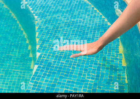Young woman testing the swimming pool temperature with her hand in the water - Stock Photo