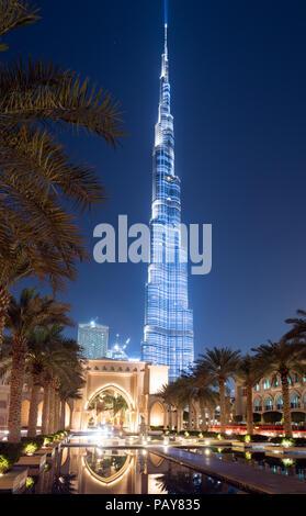 DUBAI, UAE - February 15, 2018: Burj Khalifa, with 828m height the tallest tower in the world, reflecting on the   Dubai Fountain lake outside the Dub - Stock Photo