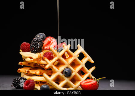 Photo of viennese wafers with berries pouring honey on black empty background - Stock Photo