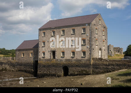 Carew Tidal Mill with Carew Castle in distance - Stock Photo