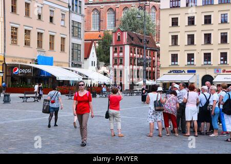 WROCLAW, POLAND - JULY 6, 2014: People visit Rynek (Market Square) in Wroclaw. Wroclaw is the 4th largest city in Poland with 632,067 people (2013). - Stock Photo