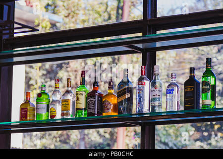 Kathmandu,Nepal - Dec 16,2017: Different brands of booze, liquor, or alcohol in a bar or tavern. Multiple bottles of adult beverages  at bar, Line of  - Stock Photo