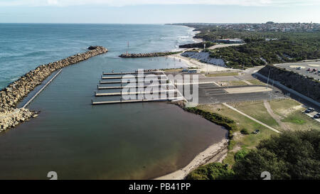 Aerial view Ocean Reef  boat harbour Perth Western Australia seaside coast waves rolling onto shore and stand up paddle boarders behind sea wall - Stock Photo