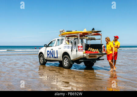 Two RNLI lifeguards and vehicle on the beach at Westward Ho!, Devon, UK - Stock Photo